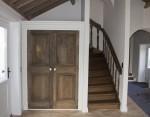 Een oude massief eiken deur gerepareerd en de andere deur nieuw bijgemaakt. Rechts een eiken trap.